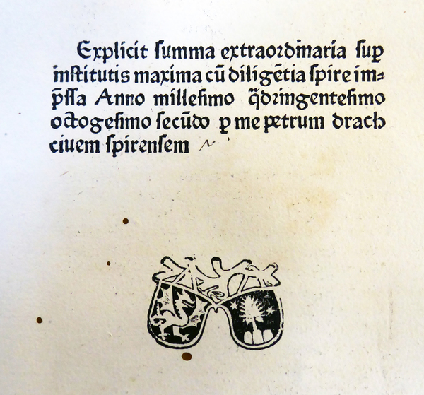 "The image shows a detail from the last page of the incunable ""Summa super Codice et Institutis"" authored by Portius Azo and printed 1482 by the workshop of Peter Drach in Speyer. The book ends with a colophon containing information about the title, printer, place, and year of printing. Below the text is Drach's printer mark. Heidelberg UB, J 1150 B Folio INC (GW 3144)."